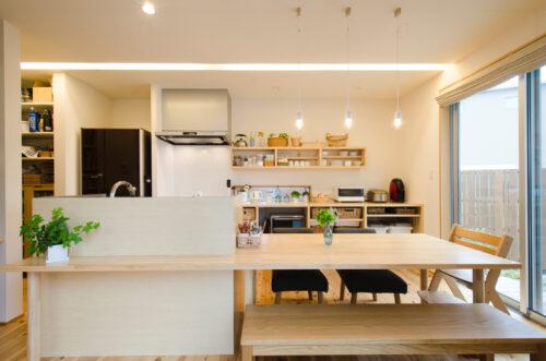家事導線を考え、IHコンロと水栓を分けたキッチン。キッチンからつながるダイニングテーブルは施主様の希望で低めに造作。
